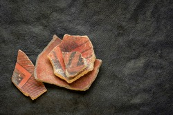 ancient Native American Indian (Anasazi) artifacts, several pottery fragments  on a dark paper background with a copy space