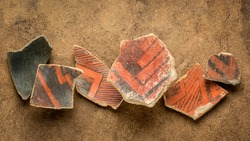 ancient Native American Indian (Anasazi) artifacts, several pottery fragments  on a textured  paper background