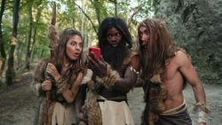 Ancient neanderthals tribe people hunting in forest looking at miracle smartphone rejoicing with future technology growling like gorillas. Multi-ethnic homo sapiens.