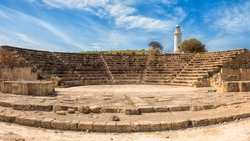 Ancient Odeon amphitheatre in Paphos Archaeological Park (Kato Pafos), harbour of Paphos, Cyprus, panoramic view. Scenic landscape with ruin of medieval architecture, lighthouse and blue sky