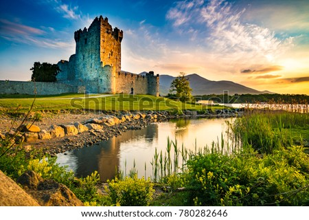Ancient old Fortress Ross Castle ruin with a lake, green grass and orange clouds in Ireland during golden hour nobody