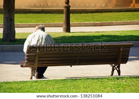 Ancient old man sitting on a bank of a public park
