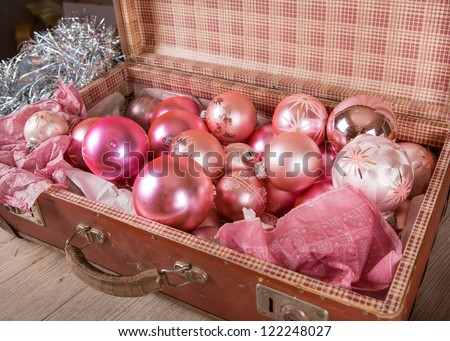 Ancient old pink Christmas tree toys in antique suitcase