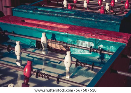 Ancient old wood classic aged Foosball table or table soccer with vintage effect photo style. Mini football close up concept.