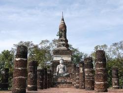 Ancient pagoda chapel and buddha statue among the ruins pillars of Wat Traphang Ngoen temple at Sukhothai Historical Park, Thailand.