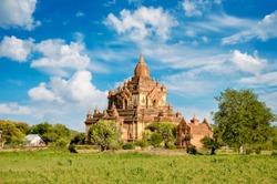 Ancient pagoda in green landscape, Bagan, Myanmar.