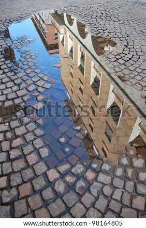 Ancient palaces reflecting in a puddle in town center, Novara, Piedmont, Italy