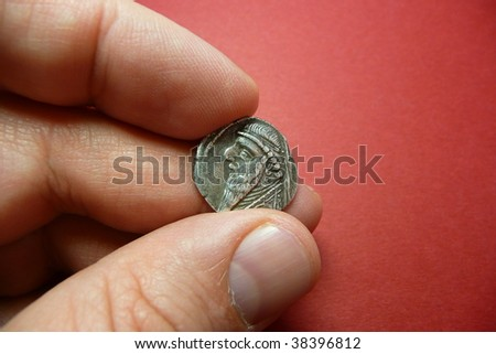 Ancient Parthian coin holded by the hand
