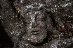 Ancient partially destroyed stone sculpture of Jesus Christ crucified on the cross.