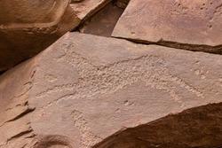 Ancient petroglyphs on rock in Sunduki mountain range at republic of Khakassia, Russia. Symbolic engravings of Deer or Horse on Devonian sandstone stone. Primitive art drawing on stone