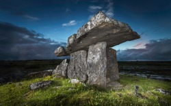 Ancient portal thomb Poulnabrone Dolmen standing on green grass in a rocky field in Glenslane Ireland lighted by flashlight before sunset with a background of blue and orange sky