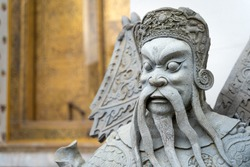Ancient portrait Chinese warrior stone doll carvings sculpture figures decorating in courtyards is the famous place and travel attraction at Wat Pho temple at Bangkok, Thailand.