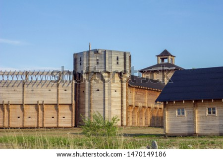 ancient reconstruction of a wooden fortress with high walls and towers