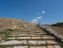 Ancient road in the ancient city of Hierapolis. The road goes into a bright blue sky. Pamukkale, Turkey.