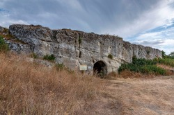 Ancient rock church from the 10th century in southwestern Bulgaria, Sakar Mountain - arched entrance dug into a sheer rock hidden among grasses and bushes