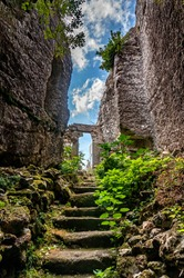 Ancient rock church from the 10th century in southwestern Bulgaria, Sakar Mountain - Entrance by stone stairs through a corridor carved into the rocks against the blue sky and sunlight