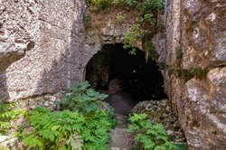 Ancient rock church from the 10th century in southwestern Bulgaria, Sakar Mountain - Entrance to the rocks leading up the stairs to a dark dungeon