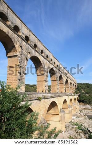ancient Roman aqueduct bridge Pont du Gard over Gard River near Remoulins in France - stock photo