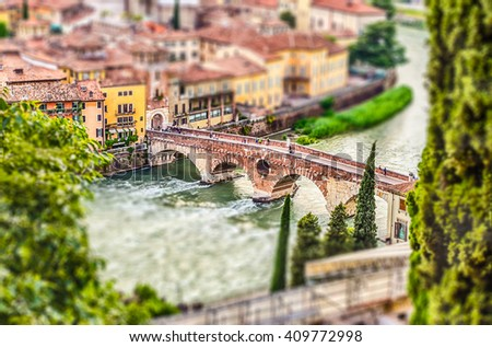 Ancient Roman Bridge called Ponte di Pietra above the Adige River in Verona, Italy. Tilt-shift effect applied - stock photo