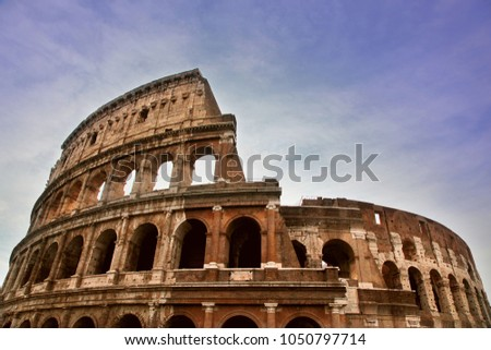 Ancient Roman Colosseum against a blue summer sky #1050797714