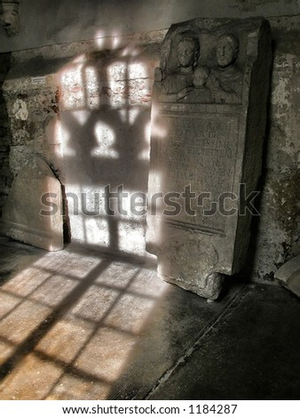 ancient Roman epitaph stone plate leaned on a wall in a museum with light and shadows of a window