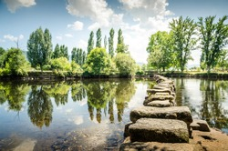 Ancient Roman stepping stones cross the Tâmega river in the city of Chaves. Portugal.