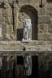 Ancient roman style marble statue of female in a wall niche with reflection in Caesarea national park vertical