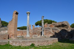 ancient roman temple in ostia antica italy with brick walls and old colums green grass and blue sky
