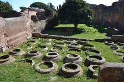 ancient roman vases in archeological site of ostia antica in backyard with grass and trees