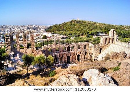 Ancient ruined Greek theatre at the Acropolis with Athens view behind