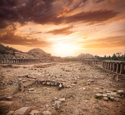 Ancient ruins of Vijayanagara Empire at dramatic sky in Hampi, Karnataka, India