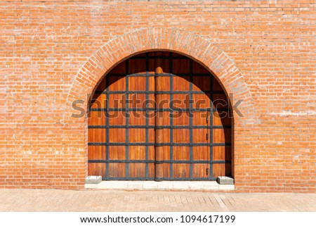 Ancient Russian wooden gate in a brick red wall of the Kremlin in Nizhny Novgorod #1094617199