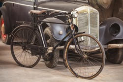 Ancient rusted bicycle and black car in an old shed