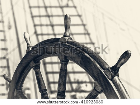Ancient ship with captain wheel in retro style. Steering wheel on the old sailboat. Sea voyage on the sailing vessel. Travel on the wooden tall ship, skipper steering wheel in front view.