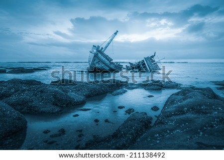 Stock Photo Ancient shipwrecks in the sea with sunset background blue color tone.