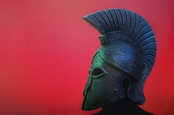 Ancient Spartan (Greek) warrior helmet on a red background with copyspace for text. Suitable for TV documentaries, history information etc.