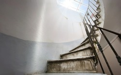 Ancient spiral staircase with marble steps and wrought iron handrail. Natural light coming in through the skylight. Architecture and circular shape