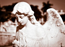 Ancient statue of a beautiful female angel with an out of focus background in sepia tones