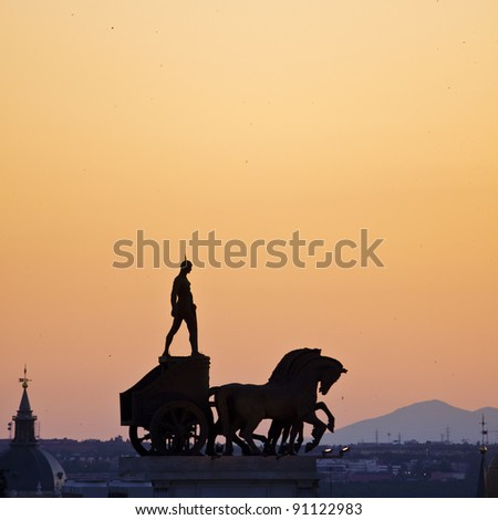 Ancient statue of a roman soldier standing on the coach on the roof of one of the buildings seen from C?rculo de Bellas Artes in Madrid, Spain. Foto stock ©