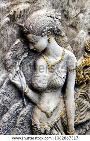 Ancient statue of an oriental woman in traditional costume and jewellery smelling a flower she holds in her hand