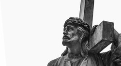 Ancient statue of Jesus Christ with cross. Selective focus on eyes. Free copy space. Horizontal image.