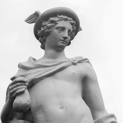 Ancient statue of the antique god of commerce, merchants and travelers Hermes (Mercury). He is olympic gods messenger with wings on his feet and helmet. Black and white image.