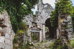 Ancient stone ruins and ivy temple wall archway at Old Bar town on Montenegro. Stari Bar - ruined medieval city on Adriatic coast, Unesco World Heritage Site.