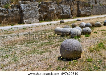 ancient stone spheres or kernels are located chaotically and abstractly on the old dry soil and one sphere in the foreground #697620310