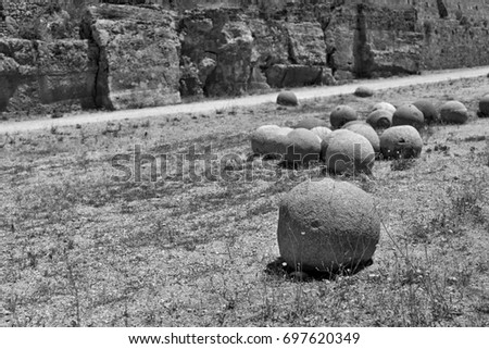 ancient stone spheres or kernels are located chaotically and abstractly on the old dry soil and one sphere in the foreground #697620349