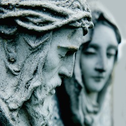 Ancient stone statue of Jesus Christ and Virgin Mary. Faith, religion, death, resurrection concept. Selective focus.