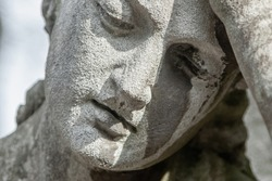 Ancient stone statue of sad man on tomb as a symbol of death, depression, pain and sorrow.