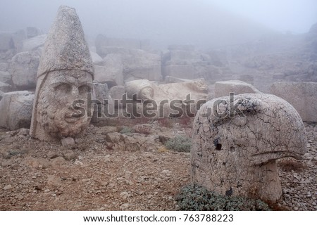 Ancient stone statues on the top of Nemrut mount, Anatolia, Turkey. In 62 BC, King Antiochus I Theos of Commagene built on the mountain top a tomb-sanctuary flanked by huge statues.