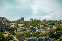 Ancient stone tomb on the island of Kekova in city of Simena, Turkey. Old concrete cemetery on the mountain. Sea tour of historical monument of architecture. Burial of ancestors closer to the sky