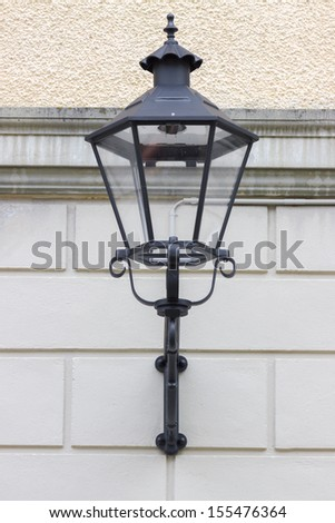 Ancient street lantern on a background of a stone wall